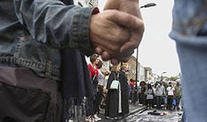 Londrinos dão as mãos antes de iniciar a limpeza no bairro de Hackney (Foto: AP