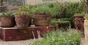 Vasos dispostos sobre um apoio de tijolos facilitam a colheita e a rega, ficam protegidos dos animais de estimação e deixam o ambiente atrativo e leve.