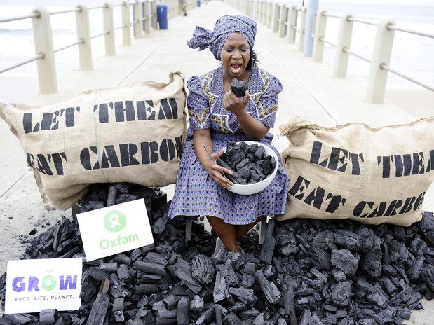 Uma ativista da instituição Oxfam finge comer um pedaço de carvão em protesto durante a Conferência do Clima || Foto: AFP