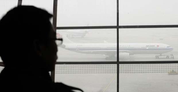 Passageiro observa avião parado no aeroporto internacional de Pequim em dezembro de 2011. Poluição extrema na capital da China já afeta movimentação aérea. (Foto: AFP)